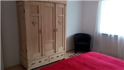 Wardrobe and a friendly sitting place in the large bedroom.