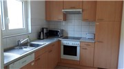 Fully equipped kitchen with microwave, dishwasher, coffee machine, toaster, glass top oven.